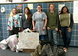 Watson HS Senior Service Committee members pose with the socks, coats, and blankets they collected.
